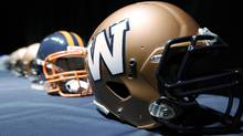 The new Winnipeg Blue Bombers 1980s-style logo is unveiled at a press conference at Canada Inn Stadium in Winnipeg, Tuesday, April 24, 2012. The CFL club is changing its helmet logo back to a simple 'W'. THE CANADIAN PRESS/John Woods (JOHN WOODS)
