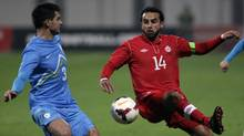 Slovenia's Gregor Balazic, left, is challenged by Canada's Dwayne De Rosario during a friendly soccer match between Slovenia and Canada, in Celje, Slovenia, Tuesday, Nov. 19, 2013. (Filip Horvat/AP)