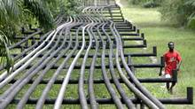 An unidentified man walks along oil pipelines in Nigeria. (GEORGE OSODI/ASSOCIATED PRESS)