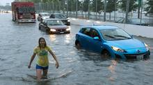 A woman walks back to her flooded car after discovering that the firetruck behind her had suffered the same fate on the Toronto Indy course on Lakeshore Boulevard in Toronto on Monday, July 8 2013. (Frank Gunn/THE CANADIAN PRESS)
