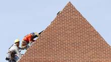 Builders work on the roof of a new housing construction site in Alexandria, Virginia October 17, 2012. (KEVIN LAMARQUE/REUTERS)