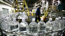 Plastic bottles filled with soda prior to being labelled are carried on conveyor belt at the soft drink maker Cott's bottling plant in this file photo. (Fernando Morales/The Globe and Mail)