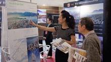 Angela Li, left, shows a picture of Vancouver to a visitor at the booth of Westbank Corp. in Shanghai, May 2, 2012. (Kevin Lee/Kevin Lee for The Globe and Mail)