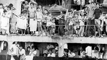 Vietnamese people fleeing a Communist dictatorship crowd the deck of a freighter in Manila harbour during the 1979 refugee crisis. (AP)