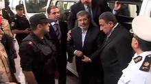 "This image made from video provided by Egypt's Interior Ministry shows ousted President Mohammed Morsi,center, arrives for a trial hearing in Cairo, Egypt, Monday, Nov. 3, 2013. Emerging from four months in secret detention, Egypt's deposed Islamist president defiantly rejected a court's authority to try him Monday, saying he was the country's ""legitimate"" leader and those that overthrew him should face charges instead (Uncredited/AP)"