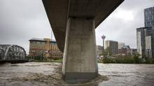 Rushing flood waters converge at the Bow River and Langevin bridge, June 21, 2013 in Calgary. Home sales in Calgary spiked in July, a phenomenon that the local real estate board says is likely a result of the June flooding. (John Lehmann/The Globe and Mail)