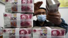 An employee counts Renminbi banknotes at a branch of Bank Of China in Changzhi, Shanxi province. (STRINGER/CHINA/REUTERS)