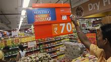 An employee changes the price tag of a product at the Big Bazaar retail store in Mumbai June 9, 2012. (VIVEK PRAKASH/REUTERS)