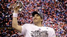 New York Giants quarterback Eli Manning holds up the Vince Lombardi Trophy while celebrating his team's 21-17 win over the New England Patriots in Super Bowl XLVI, Feb. 5, 2012. (David J. Phillip/Associated Press/David J. Phillip/Associated Press)