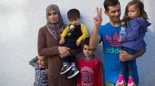 Syrian refugees who came to Canada last December, Hanan Alawwad, second left, and her husband Samer Aldhmad stand with their children Nour Aldhmad, 4, from left to right, Omar Aldhmad, 1, Ayman Aldhmad, 7, and Nawwar Aldhmad, 3, while attending an announcement at a building under construction that will house and aid refugees when it opens in April 2016, in Vancouver, B.C., on Thursday, September 10, 2015. They also have a nine-year-old son who didn't attend because he was in school. (DARRYL DYCK/THE CANADIAN PRESS)