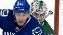 Dallas Stars goalie Kari Lehtonen (32) keeps his eye on Vancouver Canucks left wing Alex Burrows (14) during second period NHL action in Vancouver, B.C. Sunday, Nov. 17, 2013. (JONATHAN HAYWARD/THE CANADIAN PRESS)
