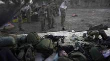 An Israeli soldier from the Golani Brigade sleeps as others, seen through a black netting, pray close to the ceasefire line between Israel and Syria on the Israeli occupied Golan Heights, in this May 7, 2013 file picture. The Israeli military denied on May 21, 2013 a claim by Syria that its armed forces destroyed an Israeli vehicle on the Golan Heights. (BAZ RATNER/REUTERS)