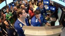 Gregg Maloney, left, and Ronnie Howard, center, both of Barclays, direct trading on the floor of the New York Stock Exchange. U.S. stocks eked out the tiniest of gains on November 12, small comfort after worries about the fiscal cliff sent the market plunging last week. (Henny Ray Abrams/AP)