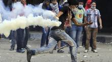 An anti-Morsi protester runs to throw a tear gas canister back, during clashes with riot police at Tahrir Square in Cairo Nov. 27, 2012. (MOHAMED ABD EL GHANY/REUTERS)