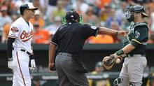 Home plate umpire Adrian Johnson, centre, separates Baltimore Orioles' Manny Machado, left, and Oakland Athletics catcher Stephen Vogt after Machado threw his bat into the infield in the eighth inning of a baseball game, Sunday, June 8, 2014, in Baltimore. (Gail Burton/AP)