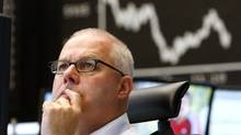 A trader watches his screens at the stock market in Frankfurt on Tuesday. The German economy, which is Europe's largest and makes up 27 per cent of euro zone output, expanded only 0.1 per cent in the quarter. (Michael Probst/Michael Probst/Associated Press)