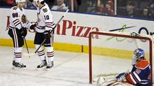 Chicago Blackhawks' Patrick Kane (L) and Patrick Sharp celebrate a goal against Edmonton Oilers' goalie Devan Dubnyk (R) during the first period of their NHL game in Edmonton April 24, 2013. (DAN RIEDLHUBER/REUTERS)