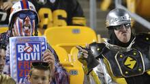 A Pittsburgh Steelers fan, right, points toward a Buffalo Bills fan during an NFL football preseason game between the teams on Saturday, Aug. 16, 2014, in Pittsburgh. (Associated Press)