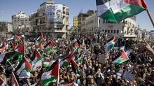 Palestinians wave flags and chant slogans during a rally calling for reconciliation between Hamas and Fatah. (Bernat Armangue/AP)