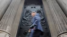 A man passes a doorway at the Bank of England in the City of London. (TOBY MELVILLE/REUTERS)