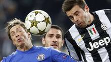 Chelsea's Fernando Torres (L) jumps for the ball with Juventus' Andrea Barzaglio during their Champions League soccer match at the Juventus stadiu