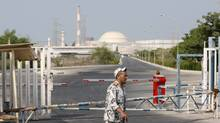 An Iranian security guard walks past a gate of the Bushehr nuclear power plant as its reactor building is seen in background, just outside the city of Bushehr, 1,245 kilometers south of the capital Tehran, Iran, Friday, Aug. 20, 2010. Russia's nuclear chief said Thursday that the planned startup of Iran's first nuclear power plant will demonstrate that Iran is entitled to peaceful use of nuclear energy under international supervision. (Vahid Salemi/AP Photo)