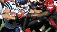 Toronto Argonauts' Chad Kackert, left, tries to break away from Calgary Stampeders' Jamar Wall during first half CFL action in Calgary on Saturday, August 18, 2012. (LARRY MACDOUGAL/THE CANADIAN PRESS)
