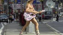 "In this Sept. 10, 2002 file photo, Robert Burck, a.k.a. ""The Naked Cowboy,"" plays his guitar in Times Square. (ROBERT F. BUKATY/AP)"