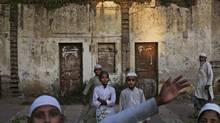 Indian Muslim boys react to the camera as they walk home from school on a street in New Delhi, India, Thursday, Sept. 27, 2012. (Kevin Frayer/AP)