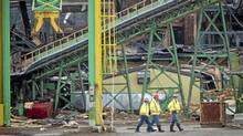 Inspectors at the Lakeland Sawmill in Prince George look over the site on April 25, 2012, after a fire and explosion at the facility. (John Lehmann/The Globe and Mail/John Lehmann/The Globe and Mail)