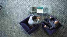 high angle view of two businessmen discussing work in an office (George Doyle/Getty Images)