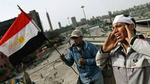 A wounded anti-government protester sounds out the Muslim call to prayer from a rooftop on the edge of Tahrir Square in Cairo, Feb. 4, 2011. (Chris Hondros/Getty Images/Chris Hondros/Getty Images)