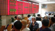 An investor, center, speaks to another while they look at the stock price monitor at a private securities company on  Aug. 3, 2012 in Shanghai, China (AP)