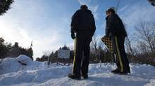RCMP officers stand on a hill looking over the U.S.-Canada border in Hemmingford, Que., on Feb. 14, 2017. (CHRISTINNE MUSCHI/REUTERS)