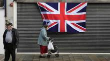 Pedestrians pass a union flag flying on a building on the Newtonards Road in East Belfast, Jan. 8, 2013. (Cathal Mcnaughton/Reuters)
