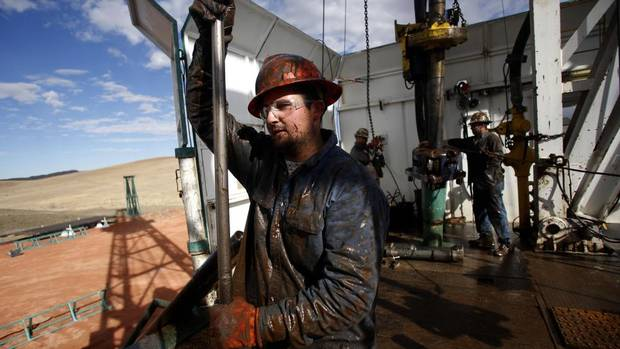 Roughneck Brian Waldner is covered in mud and oil while wrestling pipe on a True Company oil drilling rig outside Watford, North Dakota, Oct. 20, 2012. (JIM URQUHART/REUTERS)