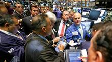 Specialist Evan Soloman, facing camera at right, is surrounded by traders on the floor of the New York Stock Exchange. (Richard Drew/Richard Drew/AP)
