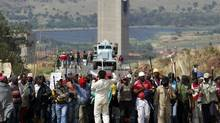 An AngloGold Ashanti security vehicle keeps watch behind striking miners at the AngloGold Ashanti mine in Carletonville, South Africa, Oct. 25, 2012. The company said on Friday that its miners had returned to work, effectively ending the strike in the country's gold sector. (SIPHIWE SIBEKO/REUTERS)