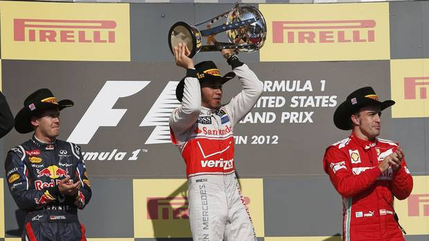 Lewis Hamilton of Britain holds up his trophy next to second place driver Sebastian Vettel (L) of Germany and third place driver Fernando Alonso of Spain during the podium ceremony after the U.S. F1 Grand Prix at the Circuit of the Americas in Austin, Texas November 18, 2012. Hamilton won the U.S. Grand Prix on Sunday while championship leader Vettel failed to clinch his third consecutive drivers' title on his 100th career start. (ADREES LATIF/REUTERS)