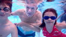 Jerry Love, who retired in 1991 after 35 years in Mississauga's recreation department, gets back in the swim of things with Benjamin Dolega, 11, and Bridget Alpe, 7. (FRED LUM/THE GLOBE AND MAIL)