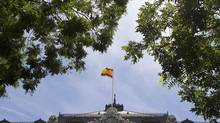 A Spanish flag flies above the Bank of Spain in Madrid on Wednesday, June 6, 2012. Spain said on Wednesday it was waiting for external auditors to put a final figure on the financial hole in its banking sector before it decides how to fund a rescue. (PAUL HANNA/REUTERS)