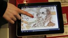 "An employee at the Czech National Bank presents an application called ""Czech Money"" on an iPad. (DAVID W CERNY/REUTERS)"