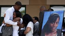 People mourn next to a photo of shooting victim Shyanne Charles following her funeral service in Toronto on Saturday, July 28, 2012. The 14-year-old was killed during a mass shooting while attending a community barbecue in east Toronto on July 16. (Michelle Siu/The Canadian Press)