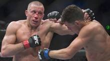 Georges St-Pierre, left, from Canada lands a blow to Nick Diaz from the United States during their UFC 158 welterweight title fight in Montreal, Saturday, March 16, 2013. (CP)