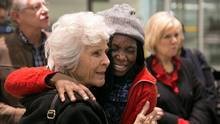 Charlene (last name withheld), a refugee from Central African Republic, hugs sponsor group member Barbara Wood of Yorkminster Park Baptist Church upon arrival in Toronto. (Melissa Tait For The Globe and Mail)