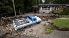 A truck lays in a sink hole outside of a home in Two Mile just outside of Sicamous, B.C. on Monday. Heavy rain falls, flooding and mudslides have caused the area to evacuated. (Jonathan Hayward/The Canadian Press)