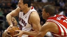 Toronto Raptors forward Hedo Turkoglu (C) drives to the basket against Houston Rockets defenders Kyle Lowry (L) and Shane Battier (R) during the first half of their pre-season NBA basketball game in Toronto October 15, 2009.REUTERS/ Mike Cassese (MIKE CASSESE)