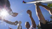 Members of Vancouver's LGBT community and Vancouver Mayor Gregor Robertson, centre, raise the rainbow flag at Vancouver City Hall on Monday to mark the start of Vancouver's Pride Week. (John Lehmann/The Globe and Mail)