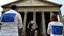 "A man holds a placard reading ""people before borders"" next to people wearing European Union flags, in front of the Pantheon in central Rome on June 20 2016, during a flashmob organised by Amnesty International in Italy. (ALBERTO PIZZOLI/AFP/Getty Images)"