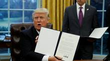 U.S. President Donald Trump holds up the executive order on withdrawal from the Trans Pacific Partnership after signing it as White House Chief of Staff Reince Priebus stands at his side in the Oval Office of the White House in Washington January 23, 2017. (Kevin Lamarque/REUTERS)